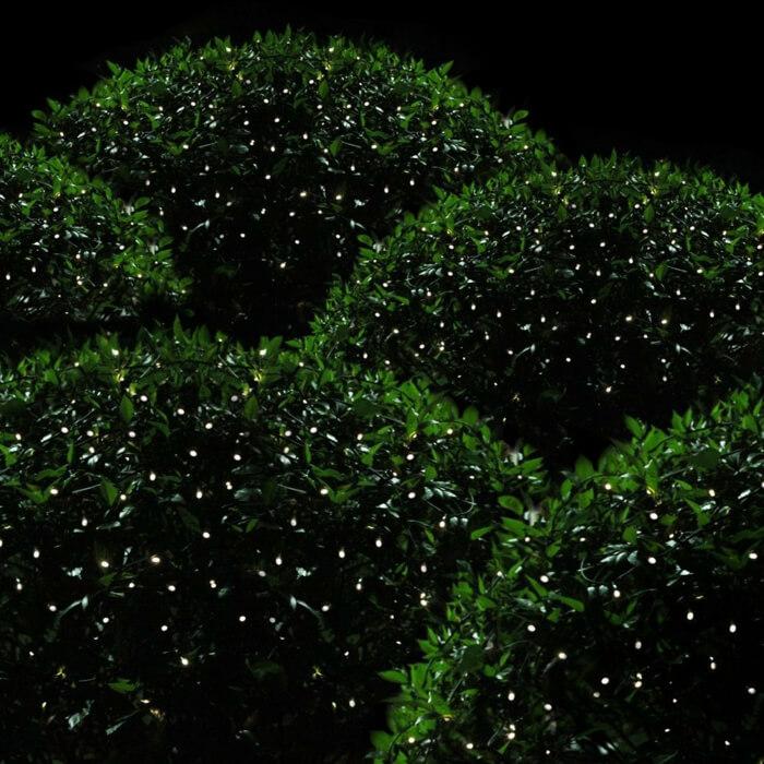 Маленькие светодиодные фонари в кустах напоминают светлячков